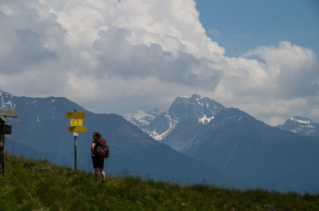 A woman reading a sign post, snow-capped mountains in the background