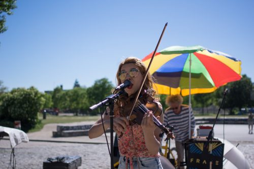 Woman playing the violin and singing on an open-air-stage in Berli